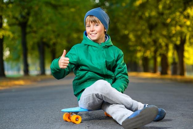 Menino sentado no skate ao ar livre