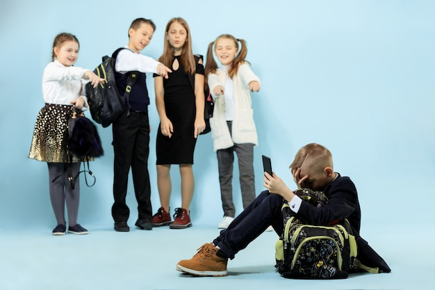 Menino sentado sozinho no chão e sofrendo um ato de bullying enquanto as crianças zombavam. triste jovem estudante sentado contra a parede azul.