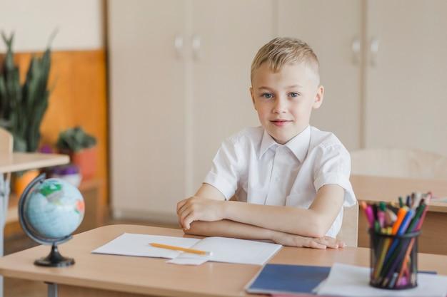 Menino, sentando, com, mãos, tabela, em, sala aula