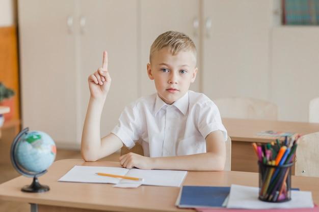 Menino, sentando, em, sala aula, levantamento, dedo