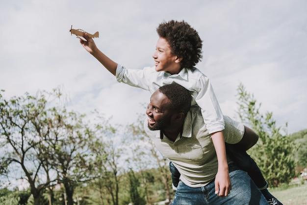 Menino, sentando, ligado, afro, pai, costas, e, jogo, com, avião