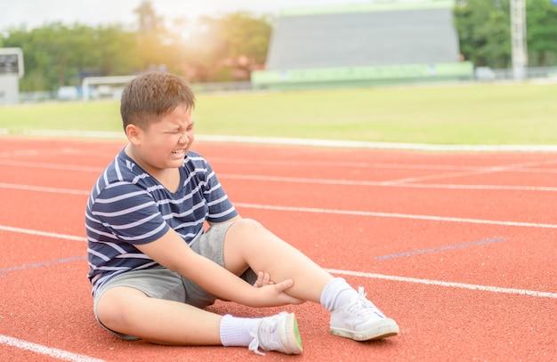 Menino sentindo dor depois de ter sua dor de bezerro