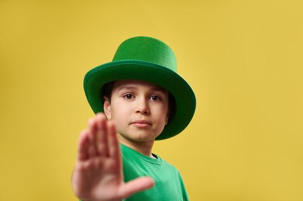 Menino sério com chapéu verde de duende irlandês mostrando stop para a câmera