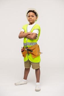 Menino sério de idade elementar vestindo uma jaqueta uniforme de reparador, cinto de ferramentas, capacete e roupa casual