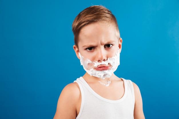 Menino sério descontente em espuma de barbear como homem