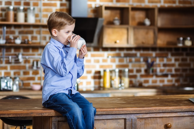 Menino simpático sentado na cozinha enquanto bebe leite