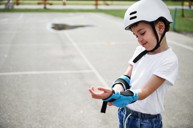Menino skatista usando capacete de segurança colocando apoios de braço de proteção antes de patinar, em pé no parquinho ao ar livre