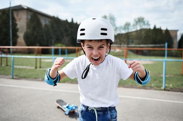 Menino skatista usando capacete de segurança gritando e mostrando os punhos olhando para a frente Foto Premium