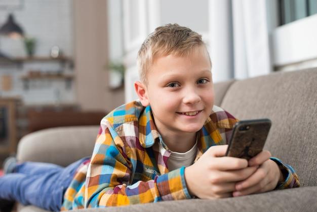 Menino, sofá, usando, smartphone