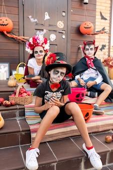 Menino sombrio com rosto pintado sentado na escada em frente à câmera contra seus amigos em fantasias de halloween