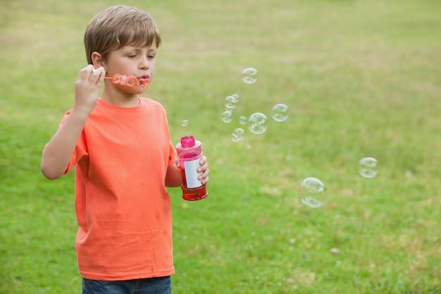 Menino soprando bolhas de sabão no parque
