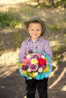 Menino sorridente ao ar livre com um chapéu de sol segurando um grande buquê de flores embrulhado em papel azul bonito