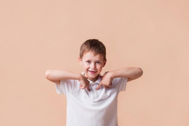 Menino sorridente apontando o dedo para si mesmo em pé perto da parede bege