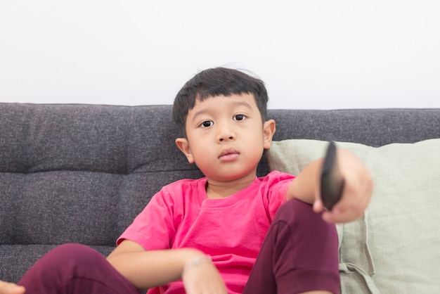 Menino sorridente assistindo tv e pressionando o controle remoto em um sofá confortável na sala de estar
