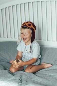 Menino sorridente bonitinho na tampa do piloto joga na cama com um pequeno avião de madeira