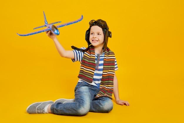 Menino sorridente brincando com um avião de brinquedo