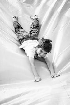 Menino sorridente brincando no escorregador inflável