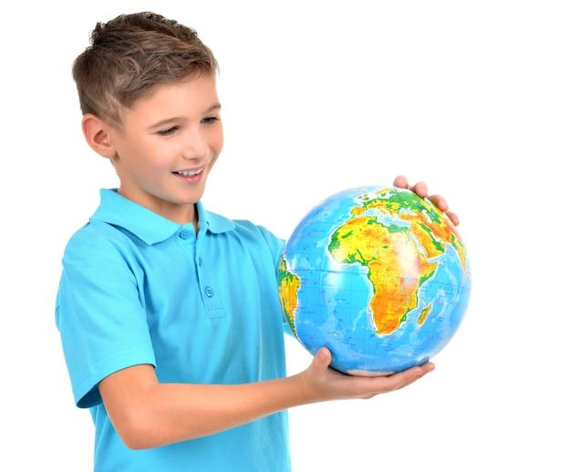 Menino sorridente casual segurando um globo nas mãos, isolado no branco