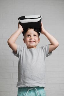 Menino sorridente, colocando no fone de ouvido virtual