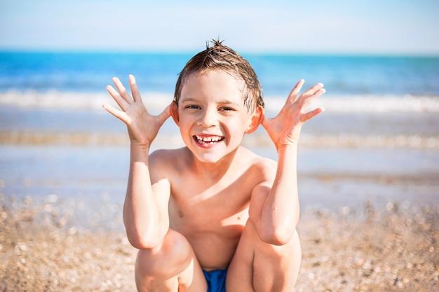 Menino sorridente com as mãos perto da cabeça sentado na praia Foto Premium