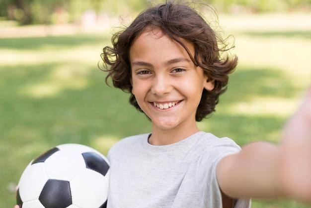 Menino sorridente com bola de futebol