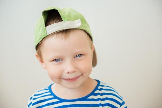 Menino sorridente com boné e olhos azuis