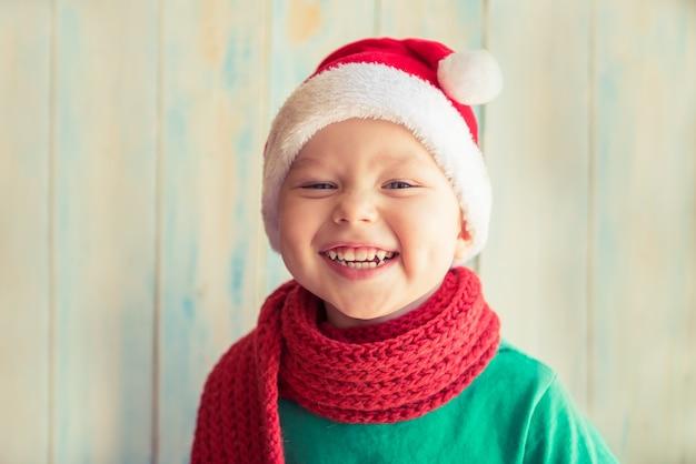 Menino sorridente com boné vermelho do papai noel