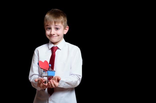 Menino sorridente com camisa leve e gravata segura um carrinho de compras de metal com um cartão postal em forma de coração dentro. isole em fundo preto.