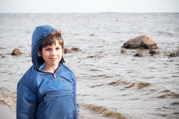 Menino sorridente com casaco azul com capuz no contexto das ondas do mar, frio e vento.
