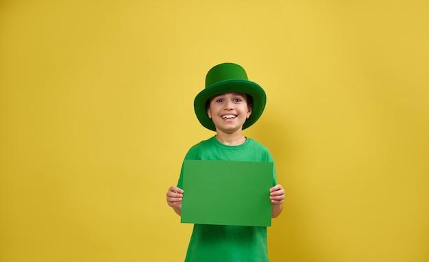 Menino sorridente com chapéu de duende irlandês verde posa com uma folha de papel verde nas mãos