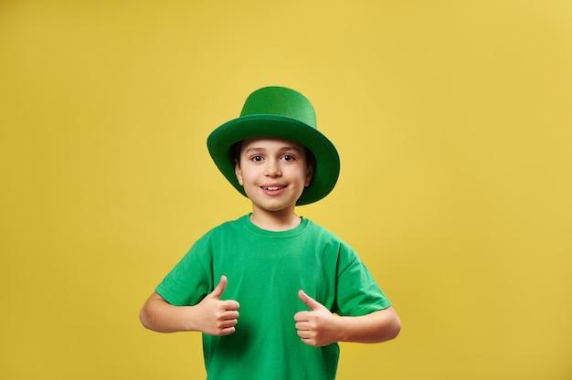 Menino sorridente com chapéu de duende verde irlandês mostrando os polegares para a câmera em pé na superfície amarela com espaço de cópia