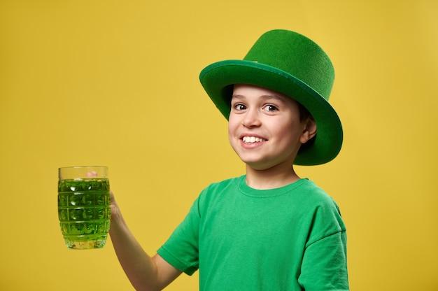 Menino sorridente com chapéu irlandês de duende verde segura um copo com bebida verde e posa para a câmera