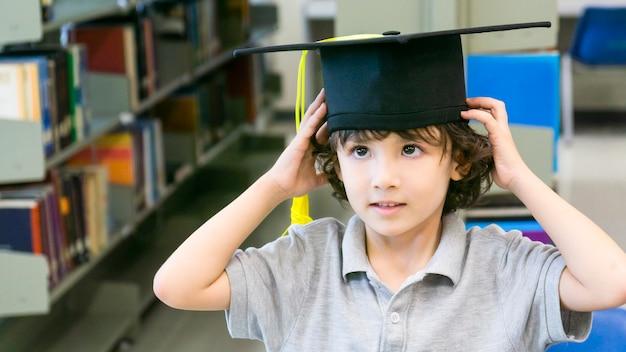 Menino sorridente com estandes de papel de cap e diploma de graduação