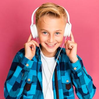 Menino sorridente com fones de ouvido, ouvindo música