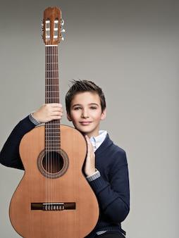 Menino sorridente com guitarra.