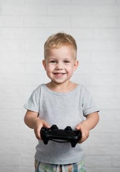 Menino sorridente com joystick, olhando para a câmera