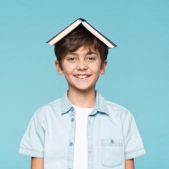 Menino sorridente com livro na cabeça