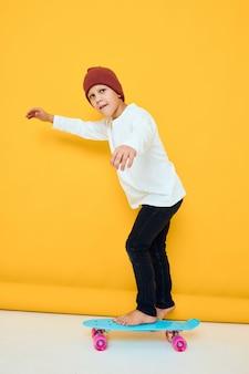 Menino sorridente com mochila vermelha azul skate fundo amarelo