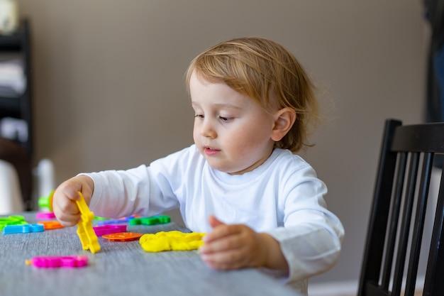 Menino sorridente com moldes de plasticina colorida na mesa