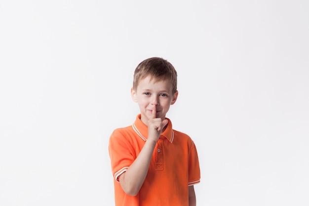 Menino sorridente com o dedo nos lábios, fazendo um gesto silencioso