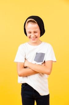 Menino sorridente com os braços cruzados usando chapéu