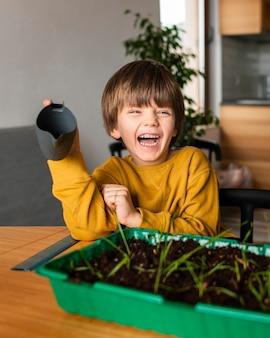 Menino sorridente com regador e colheitas em casa