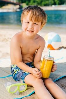 Menino sorridente com suco de vidro e sentado na praia