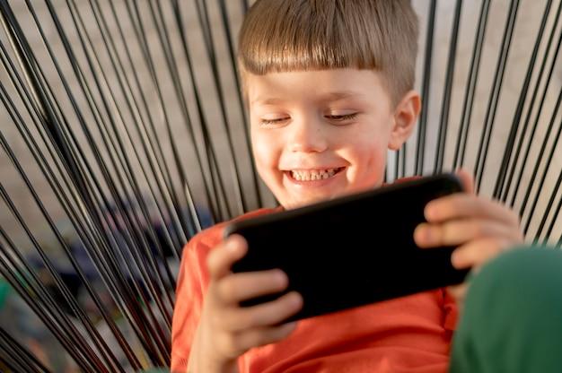Menino sorridente com tablet jogando