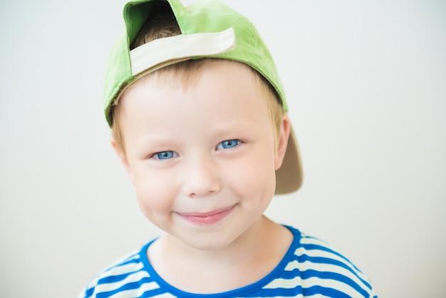 Menino sorridente com um boné e olhos azuis