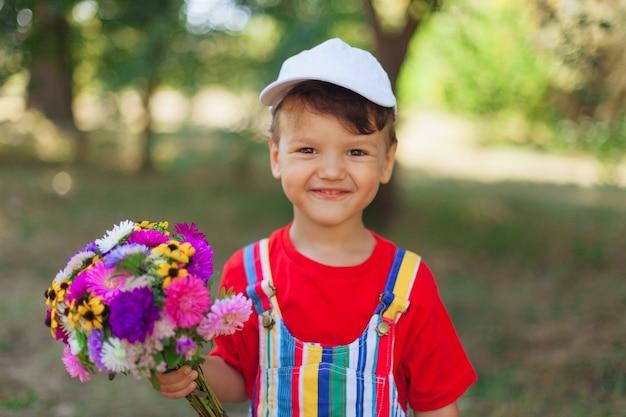 Menino sorridente com um buquê de flores silvestres, uma surpresa para a mãe no feriado, uma criança com flores em ...