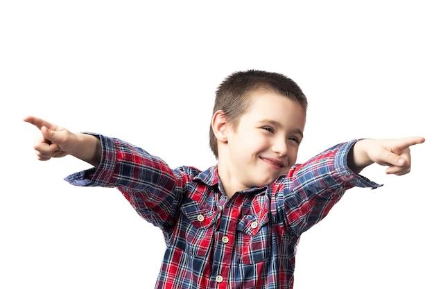 Menino sorridente com uma camisa xadrez apontando os dedos sobre um fundo branco isolado
