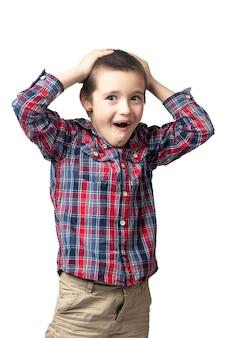 Menino sorridente com uma camisa xadrez, segurando a cabeça em um fundo branco isolado