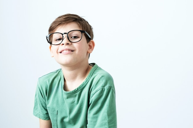 Menino sorridente com uma camiseta verde e óculos