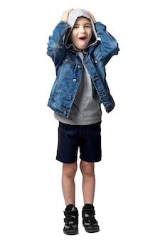 Menino sorridente com uma jaqueta jeans, segurando a cabeça em um fundo branco e isolado